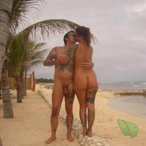 A nude friends rocking tattoos in the surf