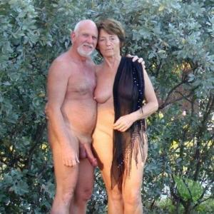 Solo nudist couple relaxing at home in the woods
