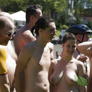 a crowd of naturists getting painted outdoors