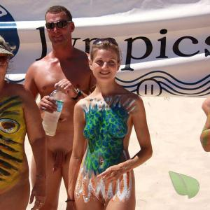a crowd of nude person wearing fun bodypaint in the surf