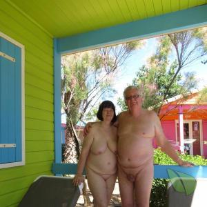 One nudist couple sitting at home in the woods