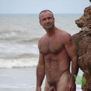 One nudist showing off their tats in the woods