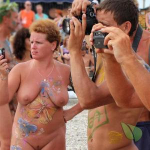 a crowd of nudists getting painted out and about
