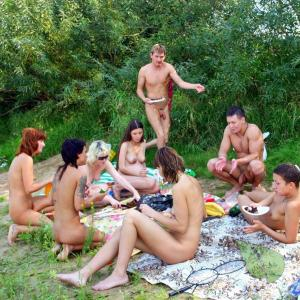 a crowd of nude people all tattooed up in the wilderness