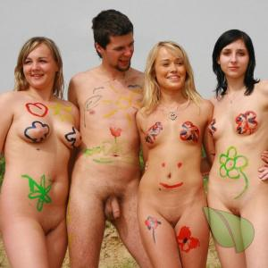 a crowd of naturists being bodypainted outdoors