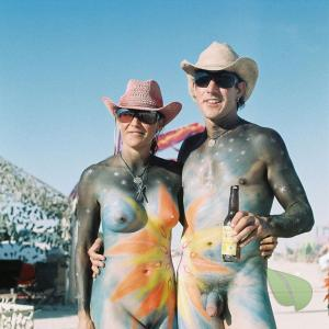 A naturist being bodypainted in the woods