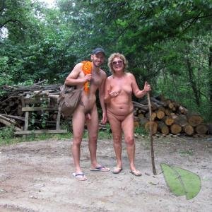 A nude person all tattooed up in the woods