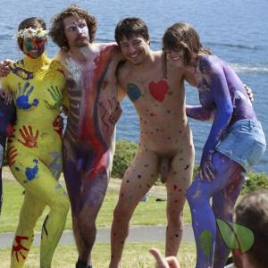 a group of nude people being bodypainted in the wilderness