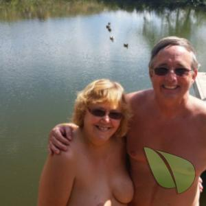 A nudist couple splashing around in the woods