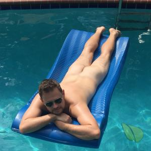 One nudist hanging out in the pool