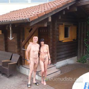 A nudist couple with cool tattoos outdoors